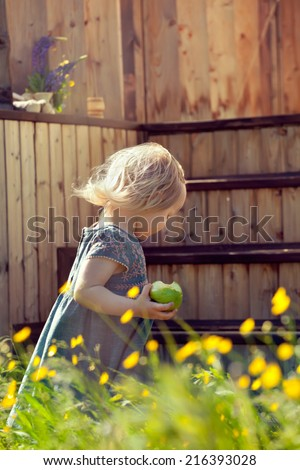 Little girl standing on a country house wooden stairs and holding an apple, natural lighting outdoor shot. Toned photo.
