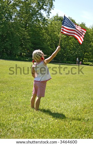 little girl standing on a lawn with USA flag in her hand