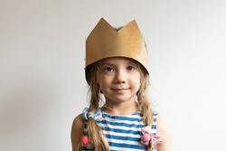 little girl stands in a golden crown