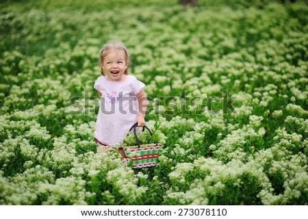 Little girl stands in a meadow with a basket of flowers and laughing