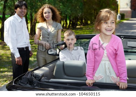 Little girl stands on backseat in cabriolet and laughs, parents stand near car - stock photo