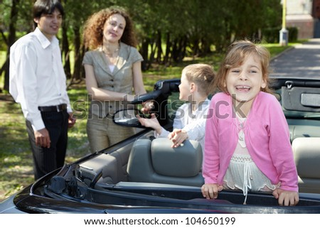 Little girl stands on backseat in cabriolet and laughs, parents stand near car and talk with boy, sitting on front seat
