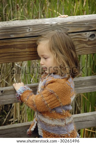 Little girl starring at a wetland,  holding a fence