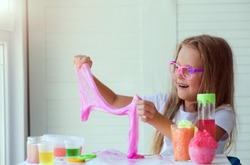 Little girl stretching pink slime to the sides. Kids hands playing slime toy. Making slime. Copyspace.