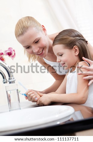 Little girl studies how to clean teeth with her mum - stock photo