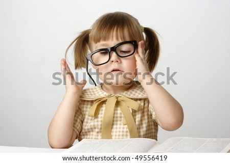 Little girl surrounded by books balancing black glasses, back to school concept
