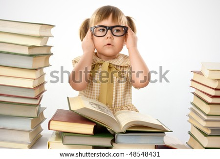 Little girl surrounded by books wearing black glasses, back to school concept, isolated over white