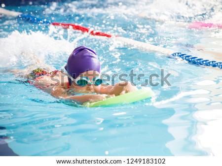 little  girl swimming in blue  pool Foto stock ©