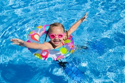little girl swimming in the pool  in inflatable ring