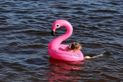 Little girl swimming in the water on inflatable circle in the shape of pink flamingo. Summer leisure, sea vacation
