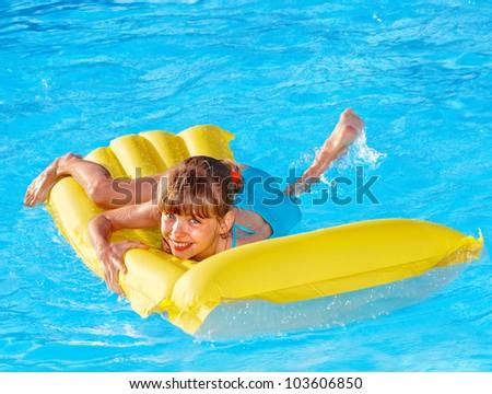 Little girl swimming inflatable beach mattress.