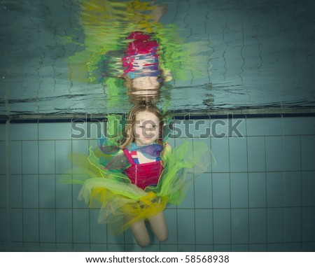 little girl swimming underwater in colorful fairy dress