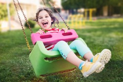 Little Girl Swinging At Playground Outdoors In Summer