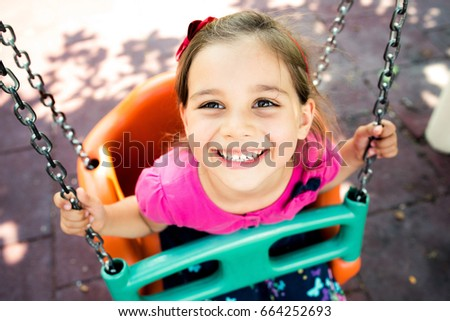 Little Girl Swinging At Playground Outdoors In Summer #664252693