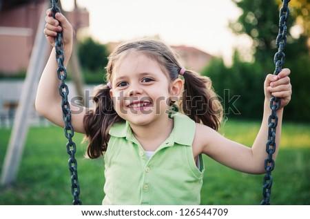 Little girl swinging close up portrait.