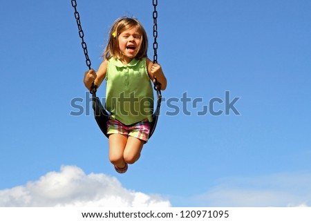 Little girl swinging high above clouds