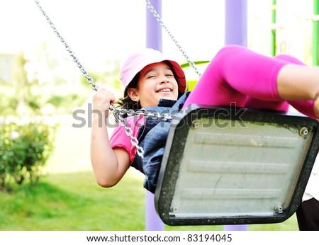 Little girl swinging in park