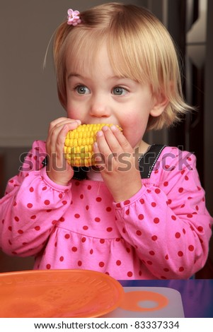 Little girl taking a bite out of a corn cob