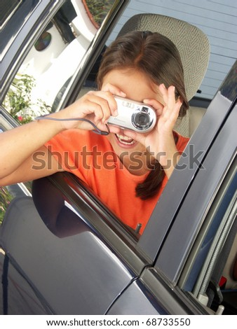Little girl taking a picture out from a car window.