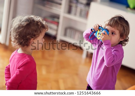 Little Girl Taking Photos Of Her Twin Sister With A Blue And Yellow Vintage Compact Camera In Living Room With Wooden Parquetry Flooring.