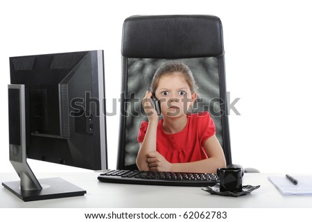 Little girl talking on the phone at the table in front of a computer. Isolated on white background - stock photo