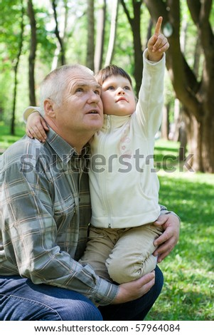 Little girl tenderly embraces grandfather in the park, sits on his arms and points up. Both look up