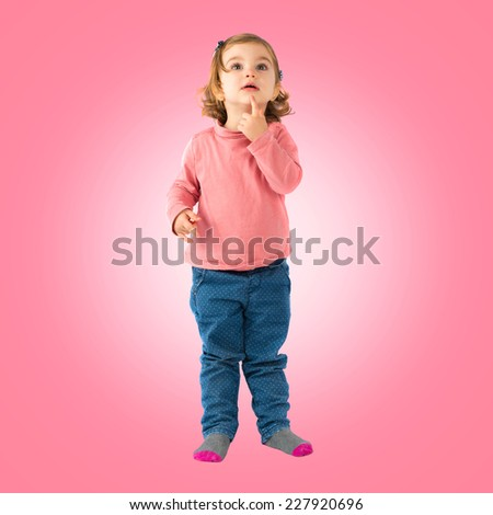 Little girl thinking over pink background