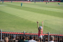 Little girl throwing her hands up during cricket game.