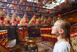 Little girl tourist enjoying interior of Man Mo Temple in Hong Kong with incense offerings and coils suspended from the ceiling