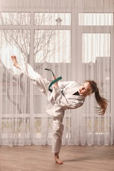 Little girl trains karate at home. Girl is engaged in training in front of a laptop. Home training in taekwondo