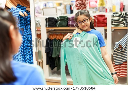 Little girl tried clothes in front of mirror in shopping mall. Asian girl smileing happy to choice and tried clothes in front of mirror in shop with copy space banner. Girl holding  clothes for tried. Foto stock ©