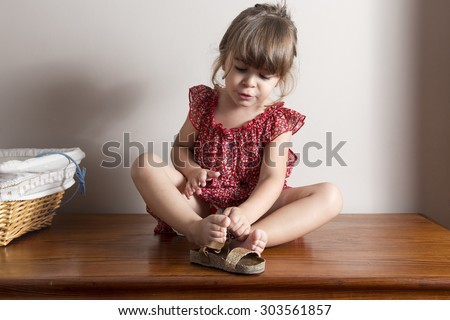 Little girl trying to put on her shoes Indoor portrait with blank space to put your own text
