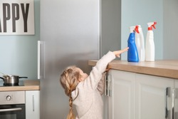 Little girl trying to reach out for bottles of detergent at home