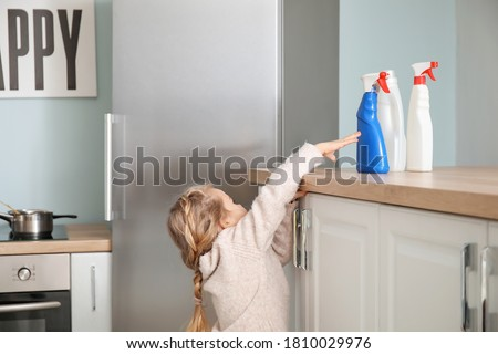 Little girl trying to reach out for bottles of detergent at home ストックフォト ©