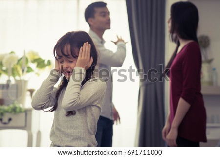Little Girl Unhappy And Crying Fighting Parents Behind. Violence and Divorce  Family concept. #691711000