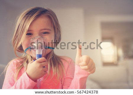 Little girl using inhaler and showing OK. Looking at camera. Space for copy.