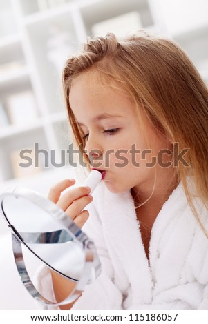 Little girl using lipstick from her mother looking at a makeup mirror