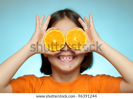 Little girl using oranges as glasses on a blue background