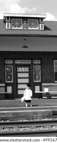 little girl waiting by tracks at depot