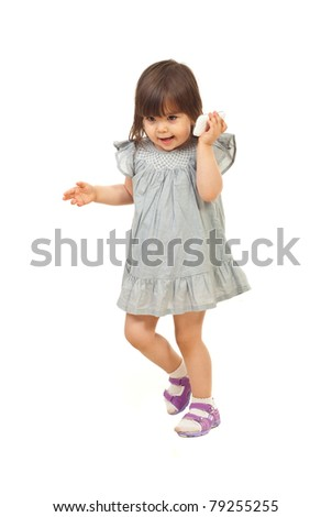 Little girl walking and talking to phone mobile isolated on white background
