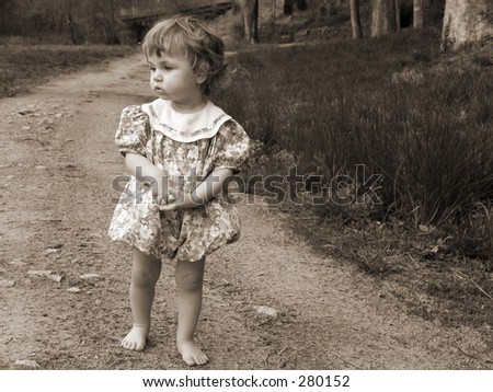 Little girl walking down a dirt road in sepia tint