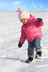 Little girl walking in a snowy landscape.