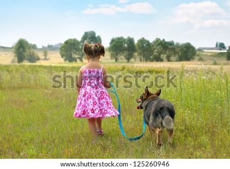 Little girl walking with dog at the meadow and keeping the dog on leash