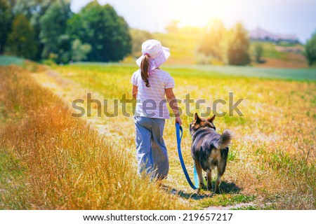 Little girl walking with dog at the meadow and keeping the dog on leash back to camera