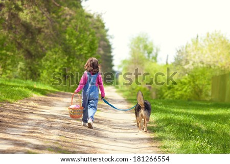 Little girl walking with dog, going to picnic and keeping the dog on leash. Back to camera.