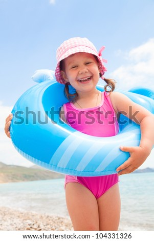 little girl wants to swim with inflatable whale on the sea