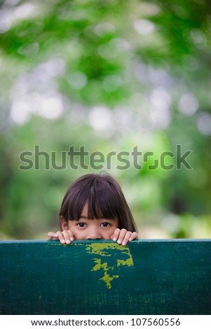 Little girl was hiding behind a chair in the park, Outdoor portrait