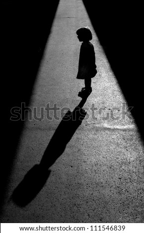 Little girl was standing in the sun between two shadows which enabled me to photograph a beautiful silhouette with a long shadow