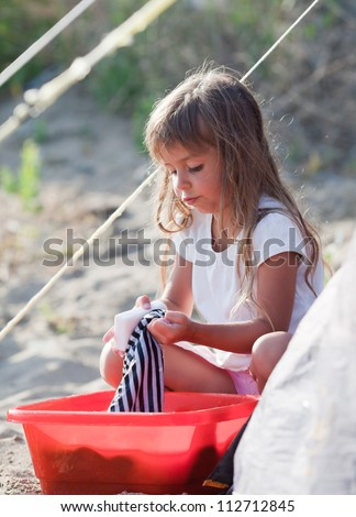 Little girl washes clothes with her hands