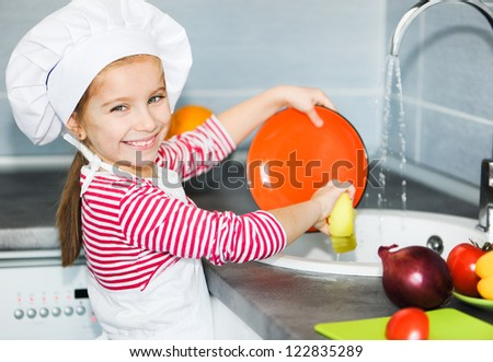 Little girl washing the dishes in the kitchen